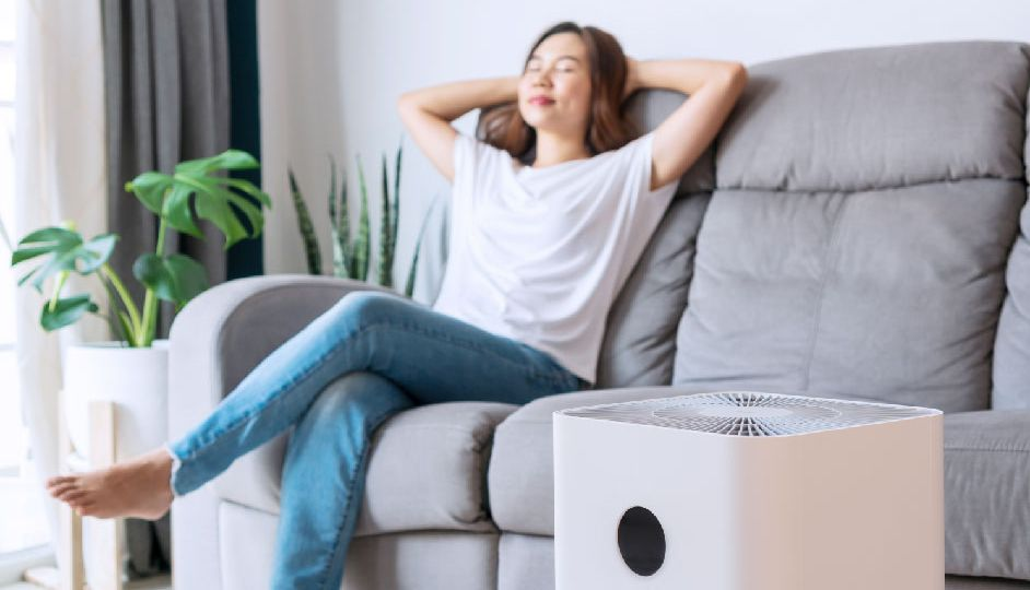 asian-woman-relaxing-comfortable-sofa-home-with-purifier-beside-01